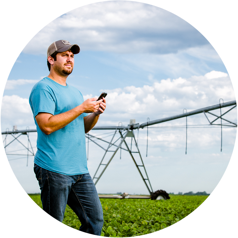 Farmer in a field with his cell phone and a pivot in the background