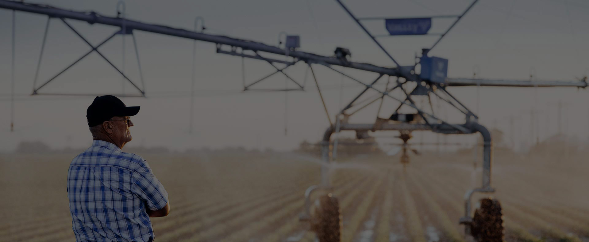 farmer in field looking at valley center pivot