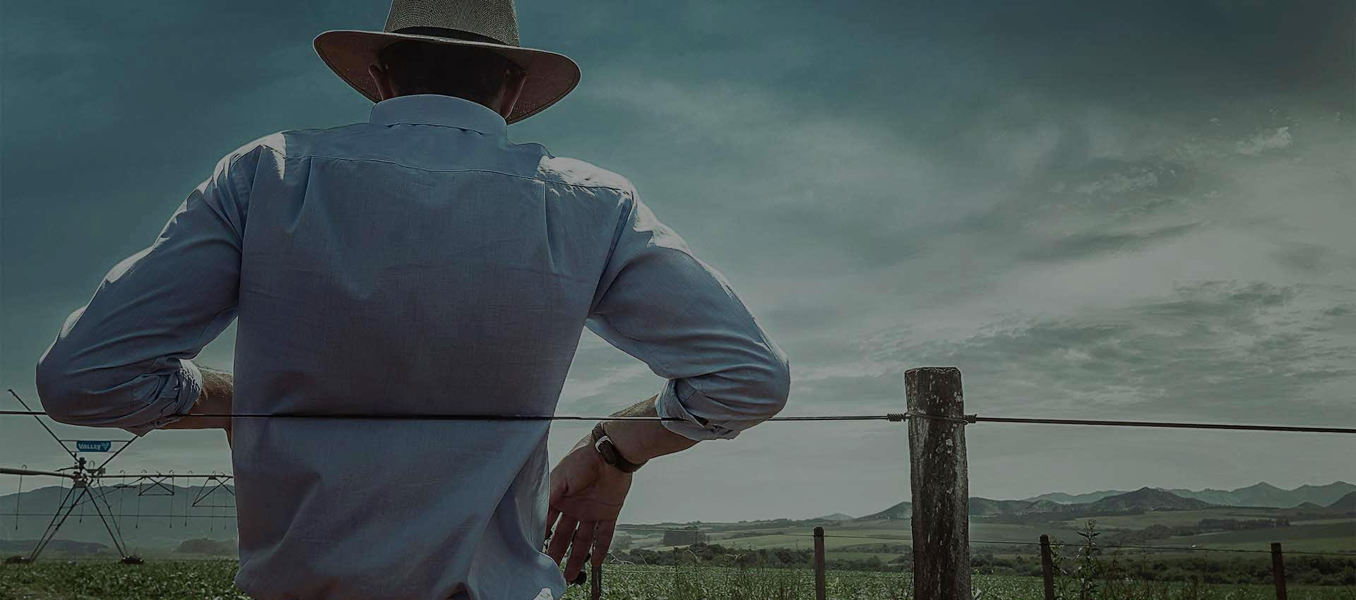 farmer leaning on a fence